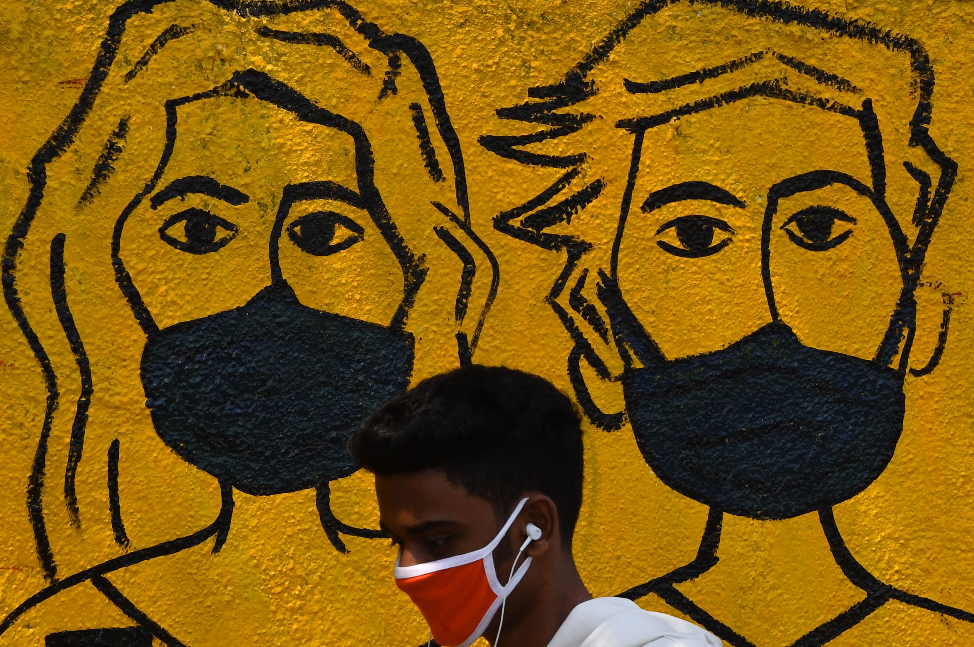 A youth wearing a facemask walk past a mural depicting people wearing famcemaks during the first day of a 21-day government-imposed nationwide lockdown as a preventive measure against the COVID-19 coronavirus, in Mumbai on March 25, 2020. - India's billion-plus population went into a three-week lockdown on March 25, with a third of the world now under orders to stay indoors, as the coronavirus pandemic forced Japan to postpone the Olympics until next year. (Photo by INDRANIL MUKHERJEE / AFP)