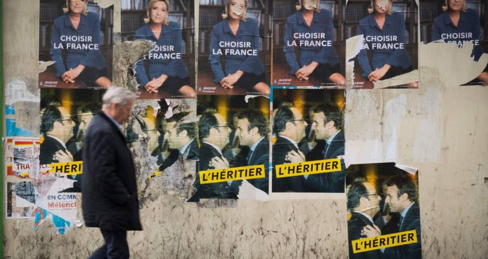 Um homem passeia em frente a cartazes com propaganda eleitoral na sexta-feira, em Paris.