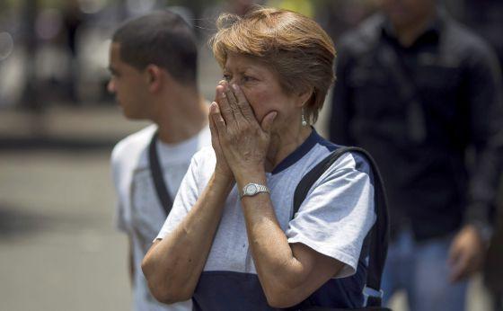 Uma mulher cobre o rosto para se proteger do gás lacrimogêneo em Caracas.