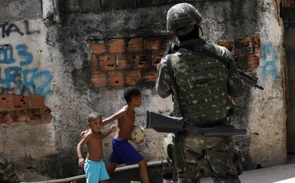 Crianças observam patrulhas das forças armadas no Rio de Janeiro.