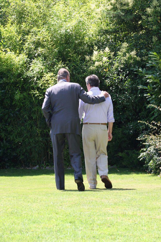 O rei Juan Carlos passeia com o ex-presidente do Governo Adolfo Suárez, doente de Alzheimer, nos jardins de sua casa durante a visita na qual os Reis lhe entregaram o Tosão de Oro, em uma foto difundida pela família. A fotografia foi agraciada com o prêmio Ortega e Gasset 2008.