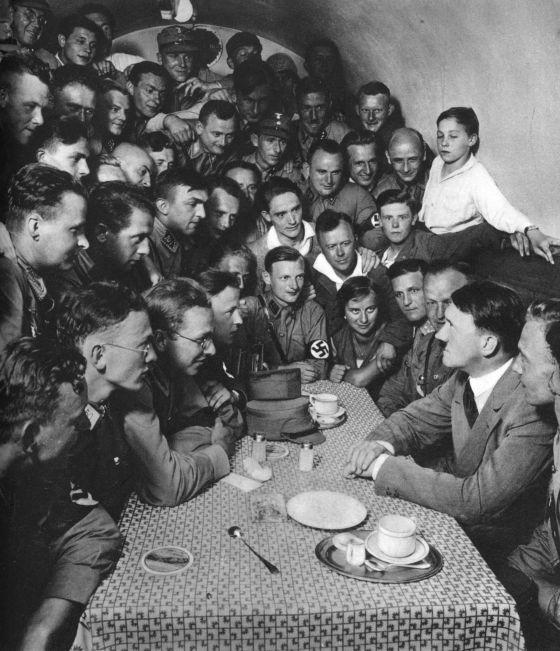 Adolf Hitler, rodeado por correligionários nazistas em uma mesa, em Berlim, em 1933.