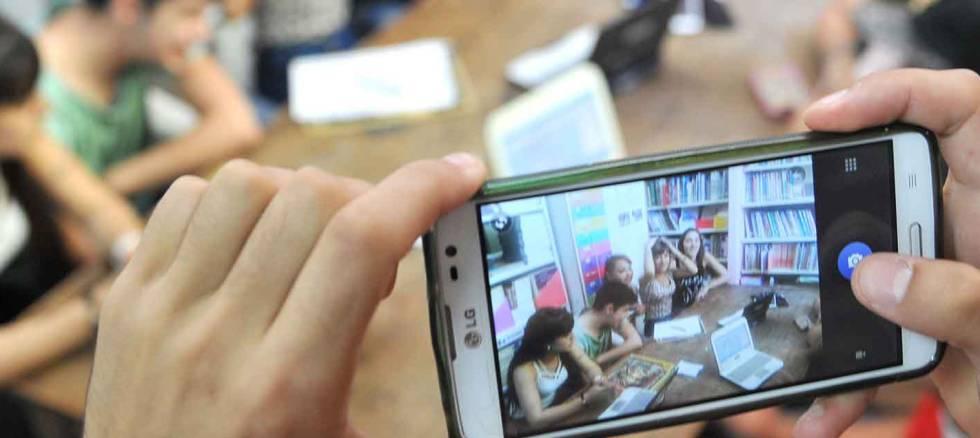 Estudantes portenhos usam dispositivos tecnológicos.
