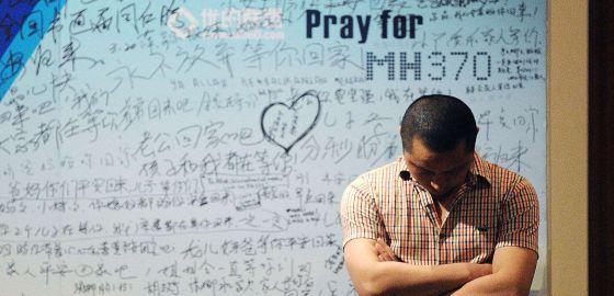 Um homem em frente a um painel com mensagens de apoio às vítimas do MH370.