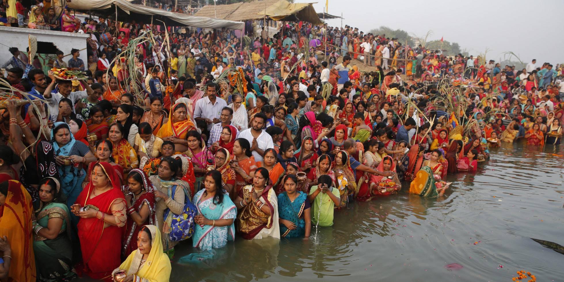 Devotos indianos rezam ao deus Sol nas águas do rio Yamuna, em Allahabad (Índia)