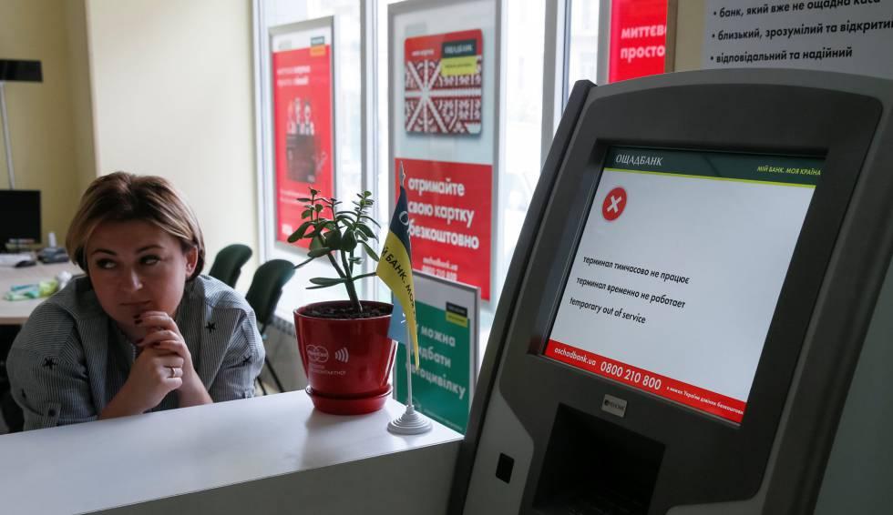 Uma funcionária do banco Oschadbank junto a um caixa afetado pelo vírus em Kiev.