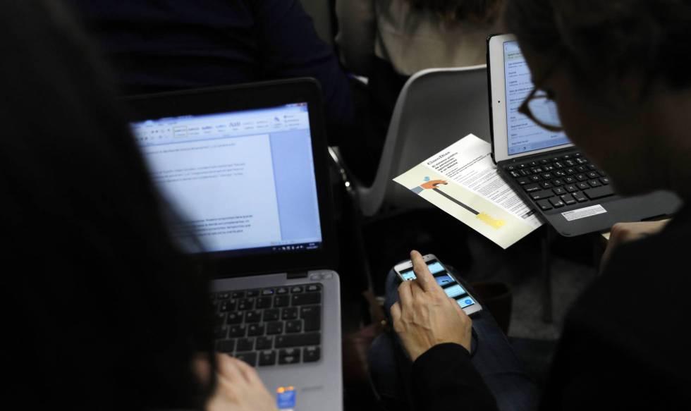 Duas pessoas trabalham com seus computadores e celulares, em uma imagem de arquivo.