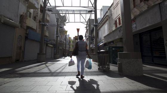 Uma mulher carrega sacolas de compras em San Juan (Puerto Rico).