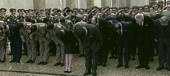 Kim Jong-un (no centro) inclina-se diante da estátua de seu pai.