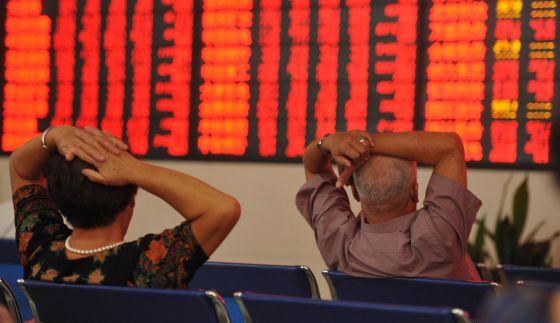Dois investidores observam um painel com cotações da Bolsa na China.