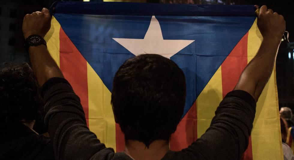 Homem segura bandeira da Catalunha.