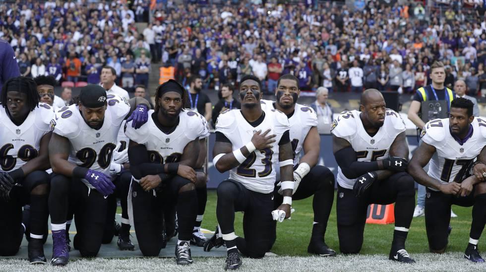 Jogadores dos Ravens se ajoelham durante a execução do hino neste domingo.
