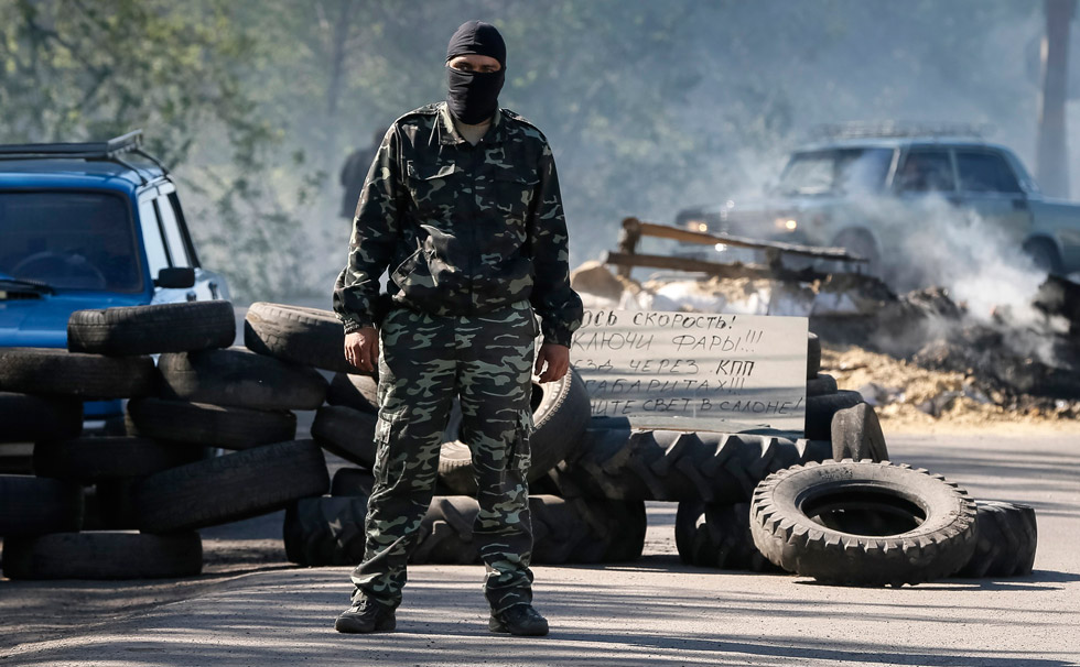 Cinco milicianos morreram hoje em confrontos armados com tropas ucranianas em Slaviansk durante a operação especial lançada por Kiev para recuperar o controle da cidade convertida no bastião do levante pró-russo no sudeste da Ucrânia. Na imagem, um partidário russo vigia um posto de controle perto de Slaviansk (Ucrânia).
