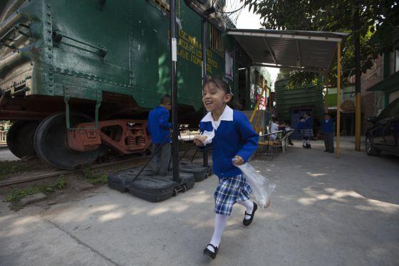 Uma aluna do último vagão-escola do México corre no recreio.