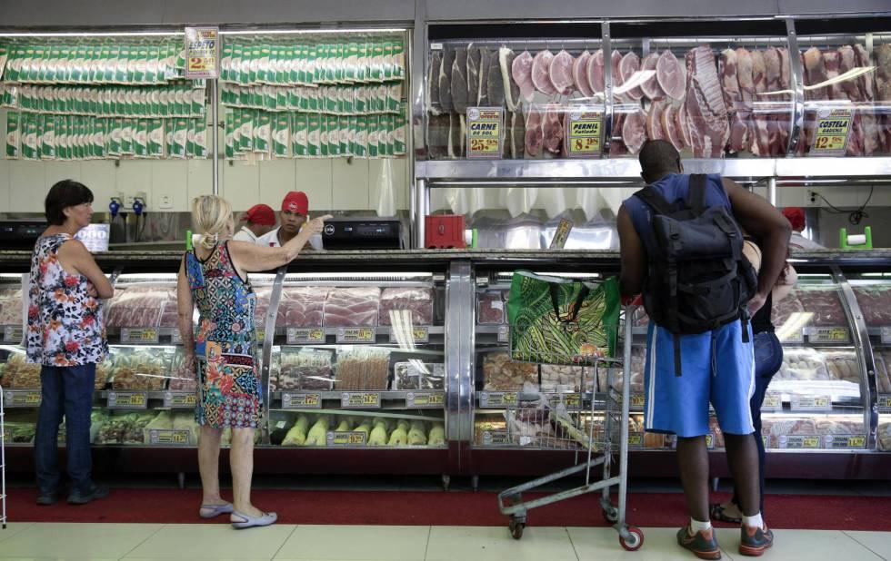 Clientes compram carne em açougue de São Paulo.