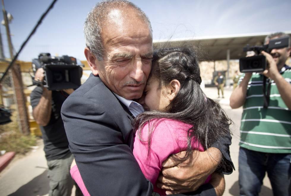 A adolescente abraça o pai no posto de controle de Jabara.