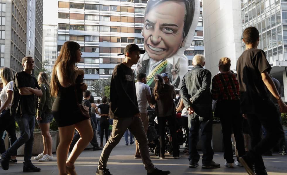 O boneco inflável de Bolsonaro entre pedestres na avenida Paulista no domingo.