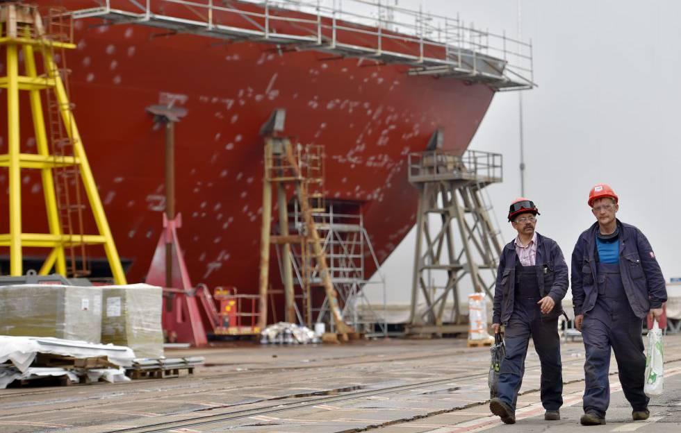 Dois trabalhadores passam ao lado de uma embarcação que está sendo consertada, em Saint-Nazaire, em setembro de 2017.
