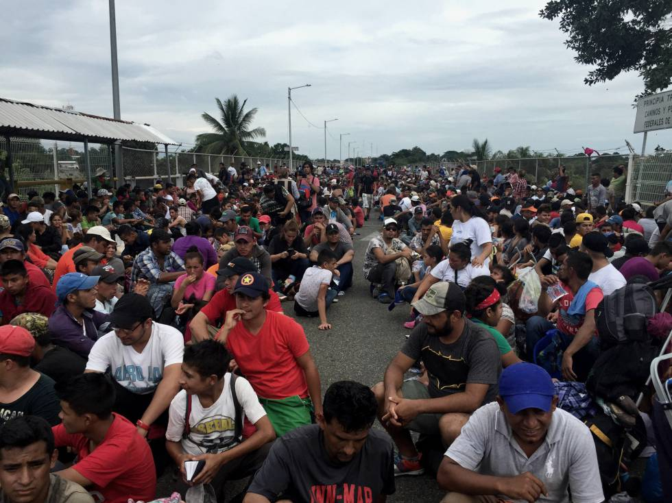 Imigrantes centro-americanos aguardam para entrar no México junto à ponte do rio Suchiate.