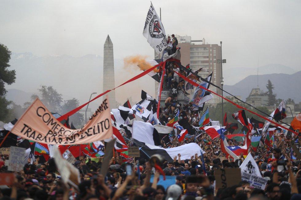 Manifestantes suben al monumento al general Baquedano durante el octavo día de protestas contra el gobierno del presidente Sebastián Piñera el 25 de octubre de 2019 en Santiago, Chile.