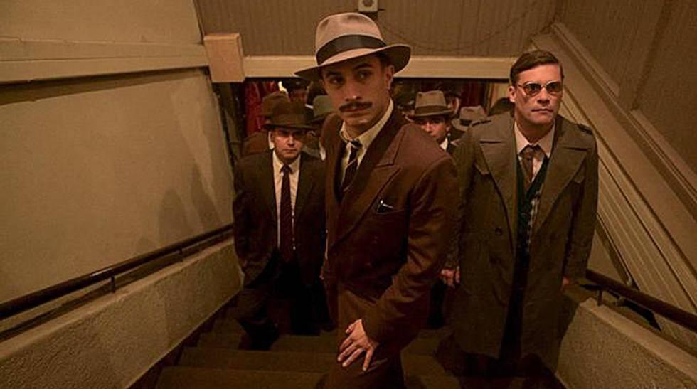 Em primeiro plano, Gael García Bernal interpretando o policial que persegue Pablo Neruda em 'Neruda'.