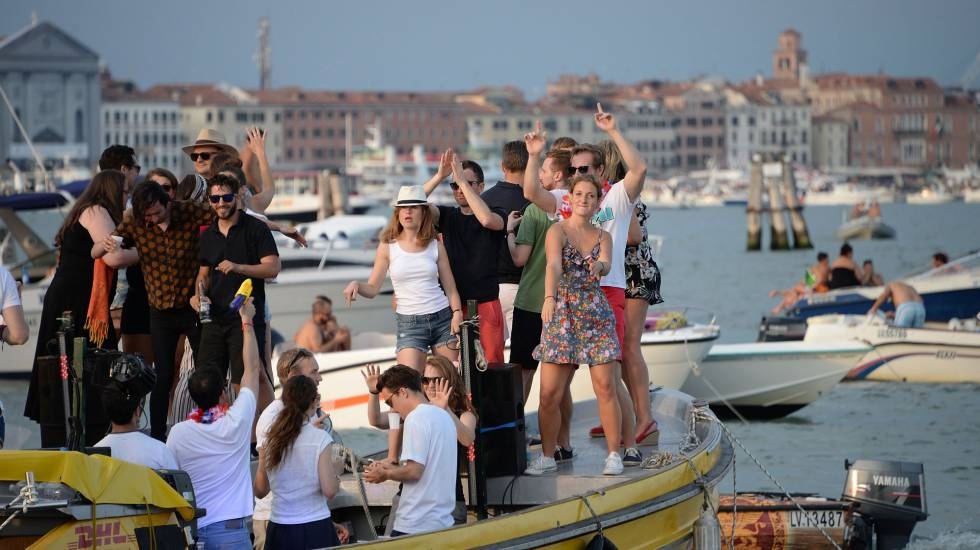 Turistas dançam em um barco, em Veneza, no dia 14 de julho de 2018.